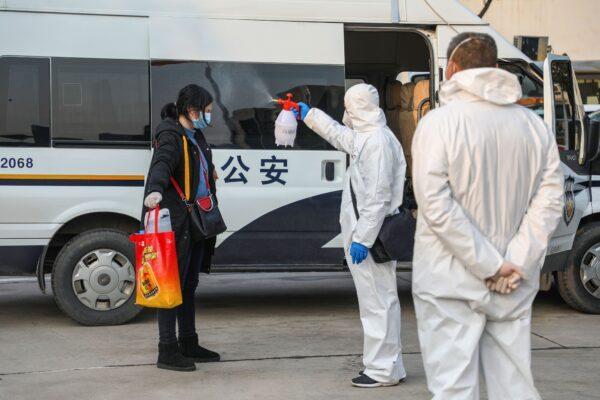 Um membro da equipe médica (C) pulveriza um paciente com desinfetante após retornar de um hospital e voltar a entrar em uma área de quarentena em Wuhan, na província central de Hubei, China, em 3 de fevereiro de 2020 (STR / AFP via Getty Images)