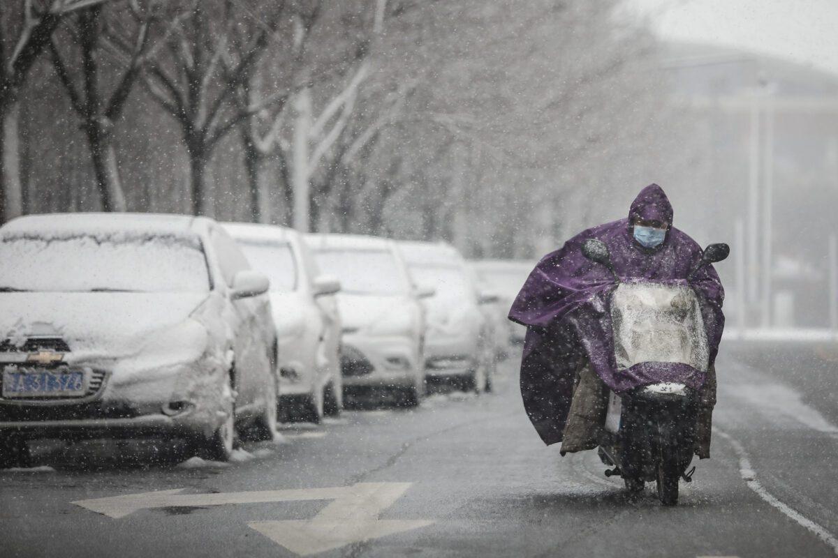 Um homem usa uma máscara protetora enquanto dirige uma motocicleta e a neve cai em Wuhan em 15 de fevereiro de 2020 (Getty Images)