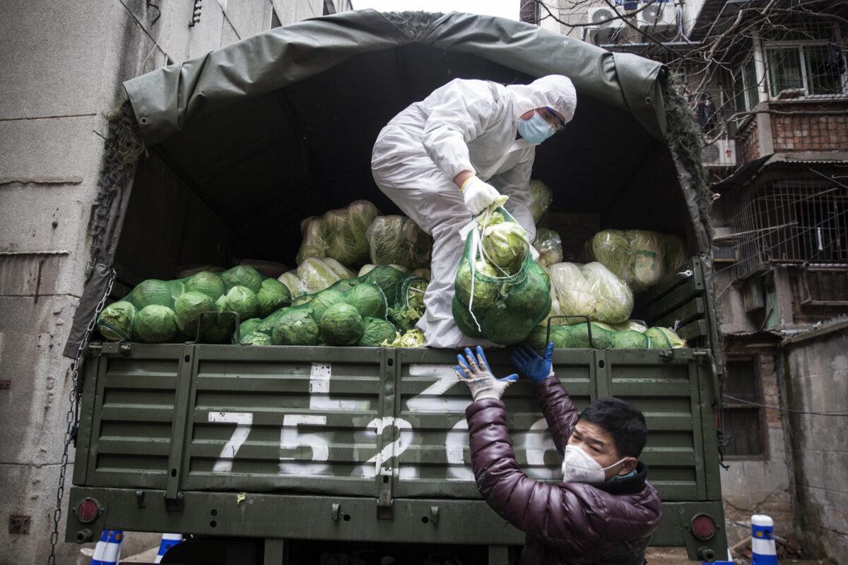 Um funcionário usa uma máscara protetora enquanto carrega legumes de caminhões em um hospital em Wuhan, China, em 10 de fevereiro de 2020 (Stringe / Getty Images)