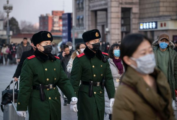 Policiais chineses usam máscaras protetoras enquanto estão em patrulha na estação de Pequim antes do Festival da Primavera anual em 22 de janeiro de 2020 em Pequim, China (Kevin Frayer / Getty Images)
