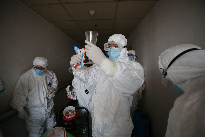 Trabalhadores se preparam para desinfetar os quartos do hospital da Cruz Vermelha em Wuhan, China, em 18 de março de 2020 (STR / AFP via Getty Images)