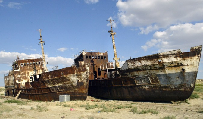 "A picture taken 04 August shows rusty shipwrecks pictured at the place called ""Sheeps cemetery"" in Dzhambul settlement, some 64 kms from town of Aralsk. The ecological disaster on Aral Sea, which had been drying up for the past 40 years, was reached in 1987, when salted lake, which had once been the world's fourth largest, split into two unequal parts. AFP PHOTO / VYACHESLAV OSELEDKO (Photo credit should read VYACHESLAV OSELEDKO/AFP/Getty Images)"
