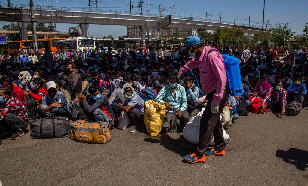 Um trabalhador de saúde indiano pulveriza desinfetante na bagagem de trabalhadores e trabalhadores migrantes, juntamente com suas famílias presas na capital nacional, enquanto esperam para embarcar em ônibus para retornar às suas aldeias nativas, enquanto o bloqueio nacional continua por causa do coronavírus altamente contagioso (COVID-19 ) em Ghaziabad, em 29 de março de 2020, nos arredores de Nova Délhi, na fronteira com o estado de Uttar Pradesh (Yawar Nazir / Getty Images)