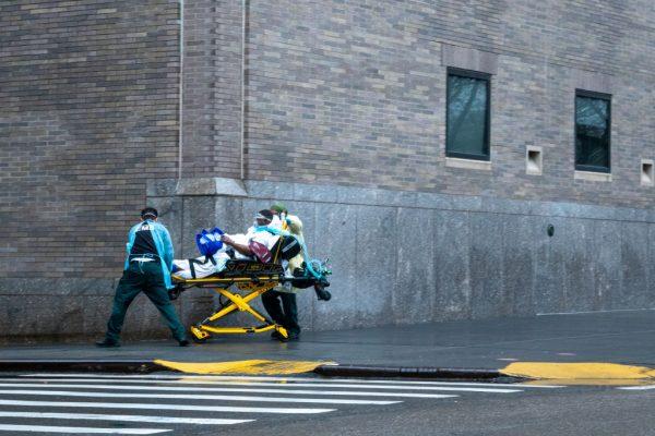 Trabalhadores dos serviços de emergência transportam um paciente na calçada do lado de fora do Hospital Mount Sinai em 13 de abril de 2020 na cidade de Nova Iorque (David Dee Delgado / Getty Images)