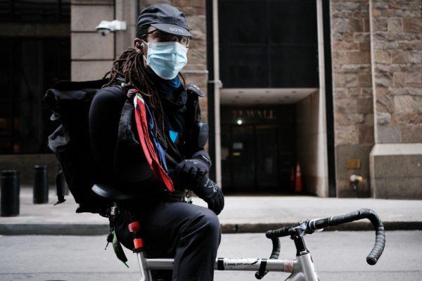 Um entregador faz uma pausa perto de Wall Street em 20 de março de 2020, na cidade de Nova Iorque (Spencer Platt / Getty Images)