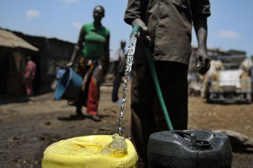 Um fornecedor de água coleta água em jerrycans para vender na favela de Mathare, Nairobi, em 22 de março de 2012, onde a escassez de água continua a ocorrer no Dia Mundial da Água (Tony Karumba / AFP via Getty Images)