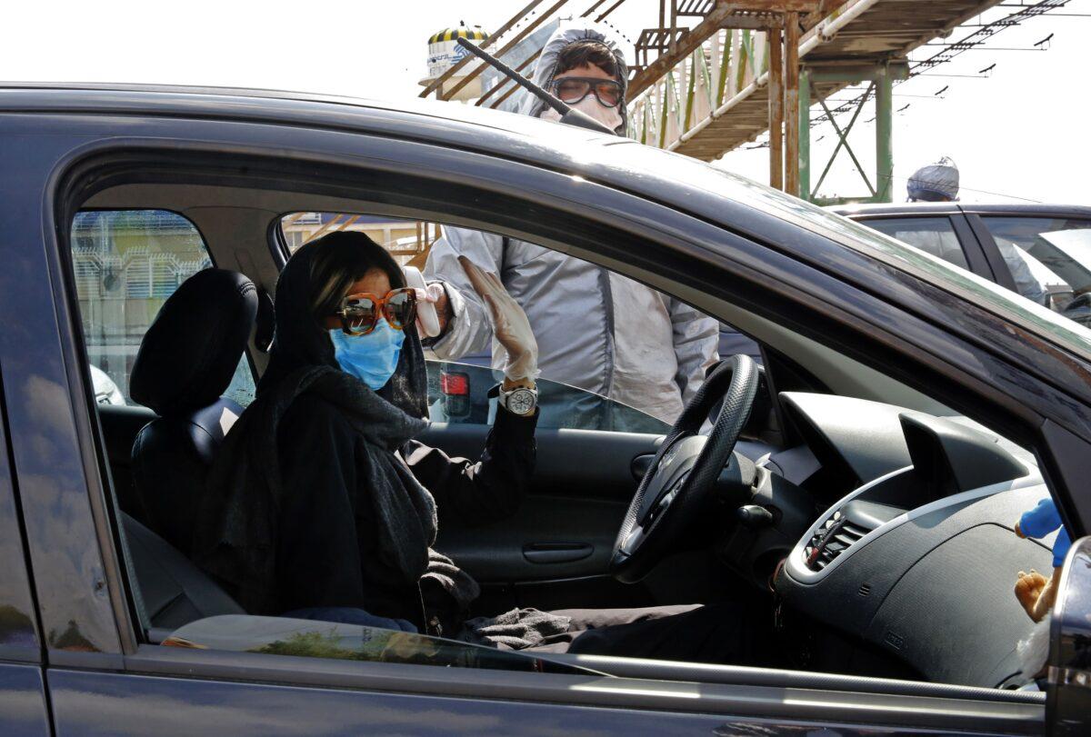 Membros do Crescente Vermelho Iraniano testam pessoas para sintomas de COVID-19 nos arredores de Teerã, Irã, em 26 de março de 2020 (STR / AFP / Getty Images)
