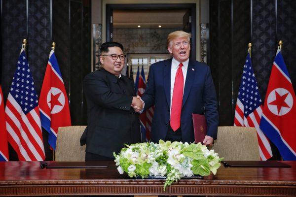Nesta fotografia de folheto fornecida pelo The Strait Times, o líder norte-coreano Kim Jong-un (E) com o presidente dos EUA Donald Trump (R) durante sua histórica cúpula EUA-RPDC no Capella Hotel na ilha de Sentosa, Cingapura, em 12 de junho de 2018 (Kevin Lim / The Strait Times / Divulgação / Getty Images)