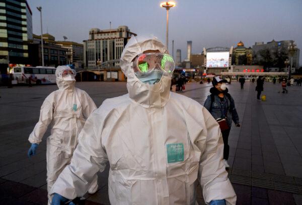 Pessoas usam máscaras faciais e roupas de proteção enquanto chegam à Estação Ferroviária de Pequim em 13 de março de 2020 (Kevin Frayer / Getty Images)