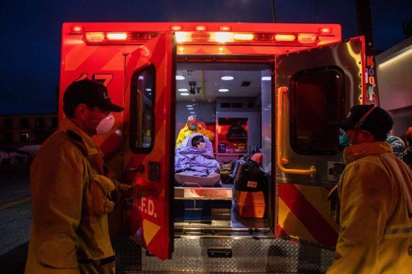 Paramédicos cuidam de uma pessoa com possíveis sintomas de COVID-19 em Los Angeles, Califórnia, em 12 de abril de 2020 (Apu Gomes / AFP / Getty Images)