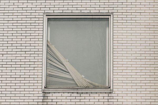Cortinas quebradas são vistas em uma janela no Brookdale Hospital Medical Center, no Brooklyn, Nova York, em 13 de abril de 2020 (Scott Heins / Getty Images)