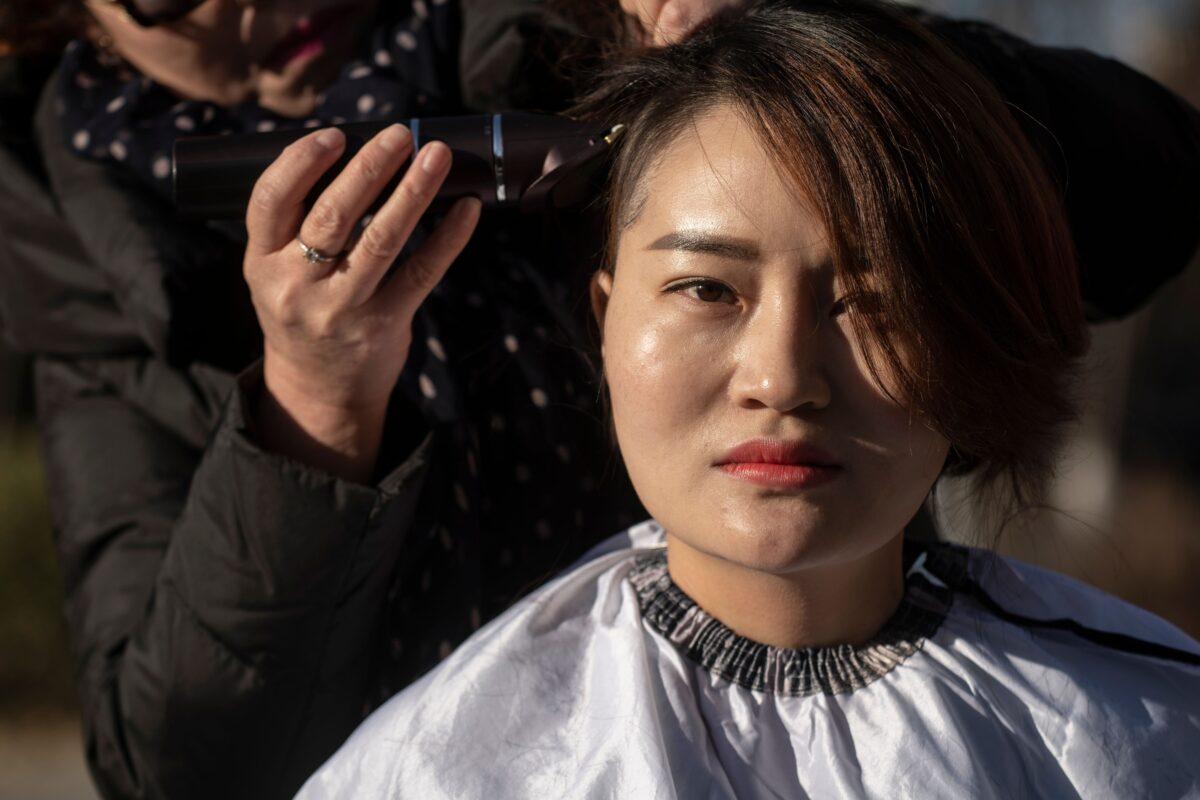 Li Wenzu raspou a cabeça para protestar contra a prisão de seu marido, o advogado chinês de direitos humanos Wang Quanzhang, detido durante a repressão do 709, em Pequim, em 17 de dezembro de 2018 (Fred Dufour / AFP via Getty Images)