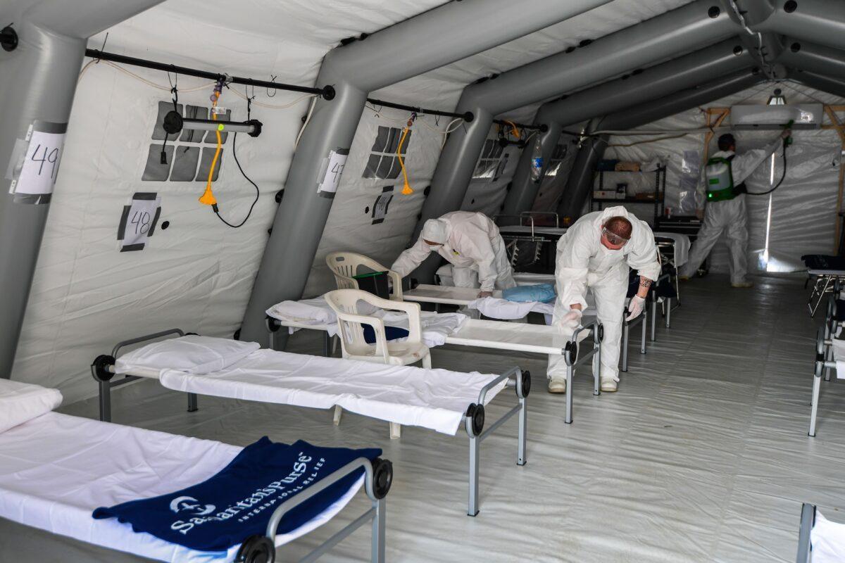 Equipe de limpeza com equipamento de proteção para desinfetar camas de pacientes em uma das lojas de um novo hospital de campanha para pacientes com coronavírus, em Cremona, sudeste de Milão, em 20 de março de 2020 (Miguel Medina / AFP / Getty Images)