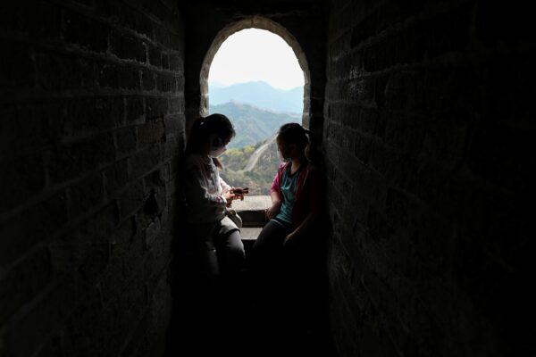 Duas crianças usando máscaras descansam durante sua visita à Grande Muralha da China, em Pequim, em 18 de abril de 2020 (Wang Zhao / AFP via Getty Images)