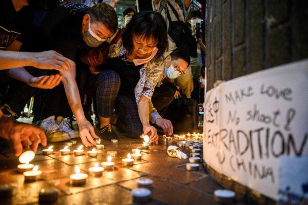 Manifestantes pró-democracia acendem velas durante uma vigília em frente ao shopping Pacific Place, na área do Almirantado de Hong Kong, em 15 de maio de 2020 (Anthony Wallace / AFP via Getty Images)
