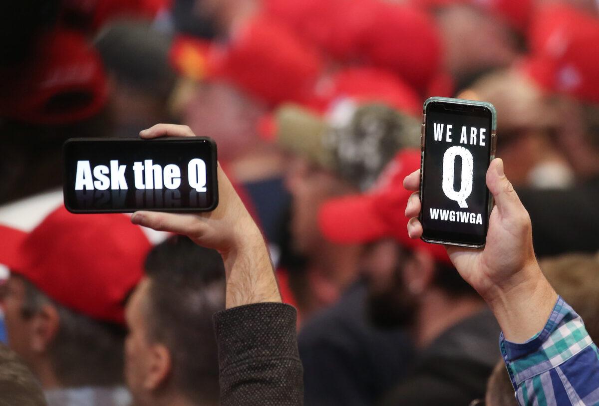 Pessoas seguram smartphones com mensagens relacionadas ao QAnon em exibição, em um comício em Las Vegas, em 21 de fevereiro de 2020 (Mario Tama / Getty Images)