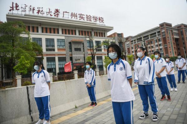Os estudantes aguardam na fila para receber o teste de ácido nucleico para o vírus do PCC em uma escola de ensino médio em Guangzhou, China, em 21 de abril de 2020 (STR / AFP via Getty Images)