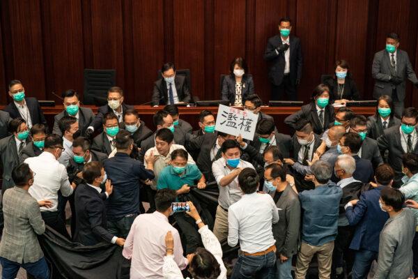 Os legisladores pró-democracia e pró-Pequim brigam na eleição de presidentes do Comitê da Câmara, presidida pelo legislador pró-Pequim Chan Kin Por no Conselho Legislativo de Hong Kong, em 18 de maio de 2020 (Anthony Kwan / Getty Images)