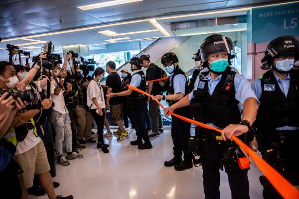 A polícia (direita) participa de uma operação de limpeza durante uma manifestação pró-democracia que pede a independência da cidade em um shopping em Hong Kong em 16 de maio de 2020 (Isaac Lawrence / AFP via Getty Images)