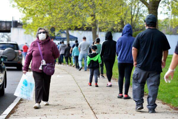 Pessoas fazem fila para obter seus kits de cuidados contendo muitos itens difíceis de encontrar, incluindo máscaras, suprimentos sanitários, itens de cuidados pessoais e materiais educacionais na Lynn Technical High School em Lynn, Massachusetts, em 16 de maio de 2020 (Joseph Prezioso / AFP via Getty Images)