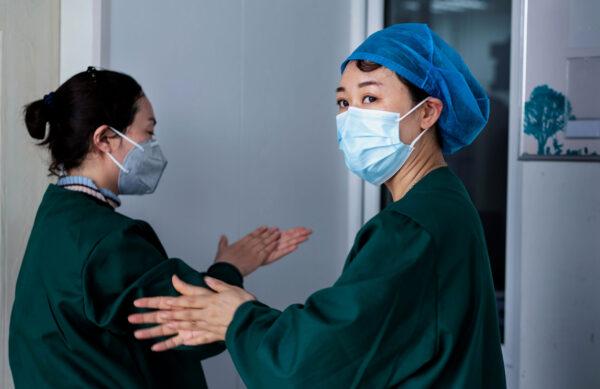 Uma equipe médica trabalha nos testes de ácido nucleico como parte das medidas de pandemia do vírus do PCC, em um centro de serviços de saúde em Suifenhe, província de Heilongjiang, nordeste da China, em 24 de abril de 2020 ( STR / AFP via Getty Images)