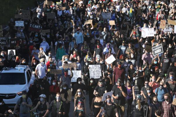 Os manifestantes marcham pela rodovia que deixa St. Paul no caminho para o US Bank Stadium em Minneapolis, através da ponte Saint Anthony Falls no quarto dia de protestos e violência após a morte de George Floyd, em Minneapolis, Minneapolis, em 29 de maio de 2020 (Charlotte Cuthbertson / The Epoch Times)