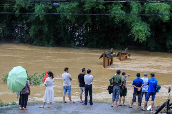 Pessoas observam uma rua submersa em Rongan, na região sul de Guangxi, na China, em 10 de junho de 2020 (STR / AFP via Getty Images)