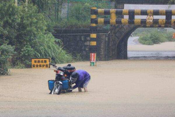 Um homem checa sua moto em meio às águas da enchente em Rongan, na região sul de Guangxi, na China, em 10 de junho de 2020 (STR / AFP via Getty Images)