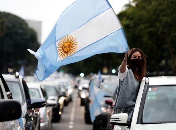 Uma mulher bate na tampa de uma panela enquanto carrega a bandeira nacional argentina durante uma manifestação pela quarentena e desapropriação da empresa de agronegócio Vicentin pelo governo do presidente Alberto Fernández no Obelisco de Buenos Aires, em 20 de junho de 2020 (Foto de ALEJANDRO PAGNI / AFP via Getty Images)