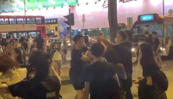 Os espectadores tentam subjugar o agressor que usava faca em Kwun Tong, Hong Kong, em 12 de junho de 2020 (Jerry / The Epoch Times)