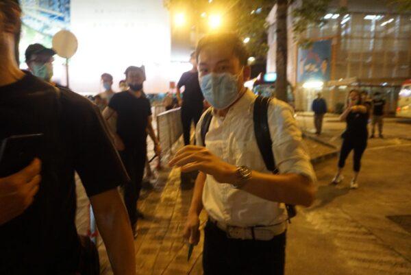 Um homem ameaça um funcionário do Epoch Times e outros cidadãos com sua faca em Hong Kong, em 12 de junho de 2020 (Jerry / The Epoch Times)
