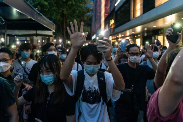 Jovens seguram as luzes do celular enquanto participam de um comício no distrito central de Hong Kong, em 9 de junho de 2020 (Anthony Kwan / Getty Images)