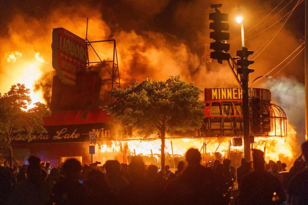 Os manifestantes se reúnem em frente a uma loja de bebidas em chamas perto da Terceira Delegacia de Polícia em Minneapolis, Minnesota, em 28 de maio de 2020 (Kerem Yucel / AFP via Getty Images)