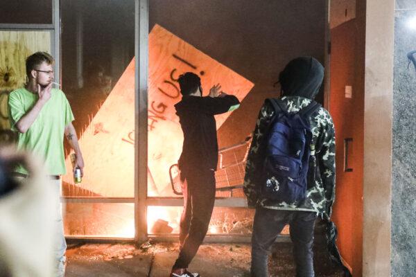 Os manifestantes atearam fogo em um banco do Wells Fargo do outro lado da rua da 5ª Delegacia de Polícia de Minneapolis durante a quarta noite de protestos e violência após a morte de George Floyd, em Minneapolis, Minnesota, em 29 de maio de 2020 (Charlotte Cuthbertson / The Epoch Times)