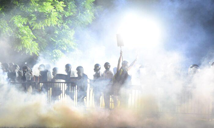 A fumaça sobe ao redor de um manifestante que levanta as mãos na frente de uma fila de policiais durante uma manifestação contra a morte de George Floyd em um parque perto da Casa Branca em Washington em 31 de maio de 2020 (Roberto Schmidt / AFP via Getty Images)