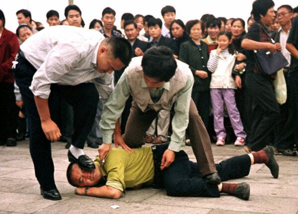 A polícia detém um manifestante do Falun Gong na Praça da Paz Celestial enquanto uma multidão presencia a cena, em 1º de outubro de 2000 em Pequim (AP / Chien-min Chung)