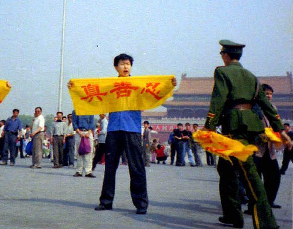 """Um policial chinês aborda um praticante do Falun Dafa na Praça Tiananmen, em Pequim, enquanto segura uma faixa com os caracteres chineses por """"verdade, benevolência e tolerância"""", os princípios básicos do Falun Dafa (Minghui.org)"""
