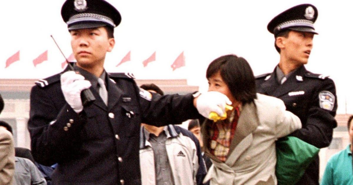 Dois policiais chineses prendem um praticante do Falun Dafa na Praça Tiananmen, Pequim, em 10 de janeiro de 2000 (Minghui.org)