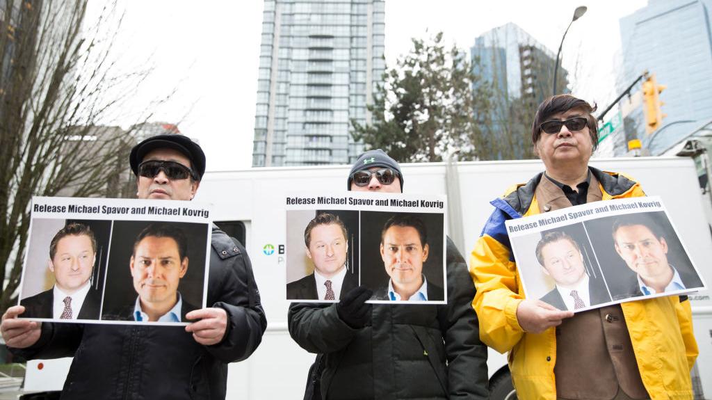 Manifestantes mantêm fotos dos canadenses Michael Spavor e Michael Kovrig, que foram detidos pelo regime chinês, do lado de fora da Suprema Corte da Colúmbia Britânica em Vancouver, enquanto a diretora financeira da Huawei, Meng Wanzhou, aparece no tribunal em 6 de março de 2019 (JASON REDMOND / AFP via Getty Images)