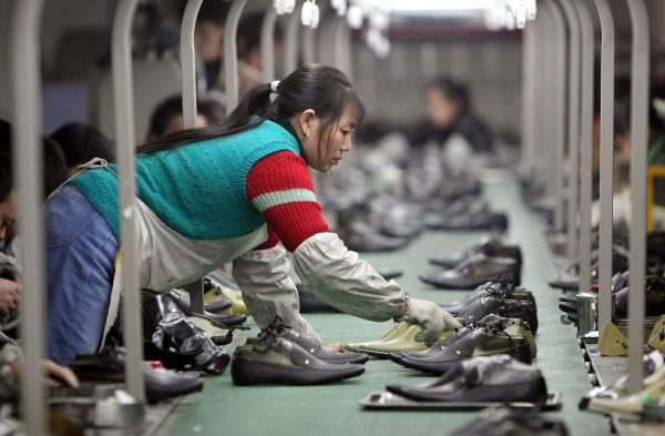 Uma funcionária tira um par de sapatos de uma linha de produção em uma fábrica localizada em Chengdu, China (Fotos da China / Getty Images)