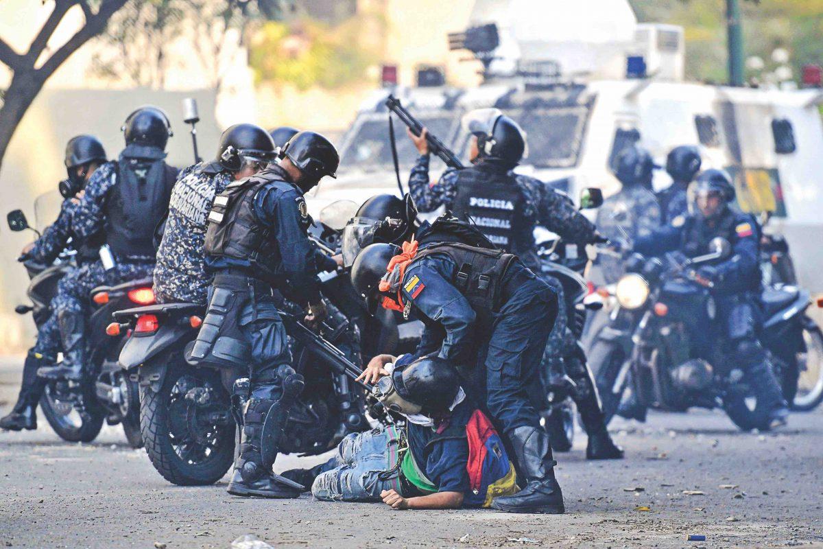 Um manifestante anti-Maduro é detido pelas forças de segurança durante os confrontos em Caracas em 1 de maio de 2019 (FEDERICO PARRA / AFP / Getty Images)