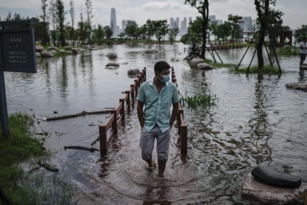 Um morador usa uma máscara facial enquanto caminha pelo Parque Jiangtan, que foi inundado devido a fortes chuvas ao longo do rio Yangtze em Wuhan, China, em 8 de julho de 2020 (Getty Images)