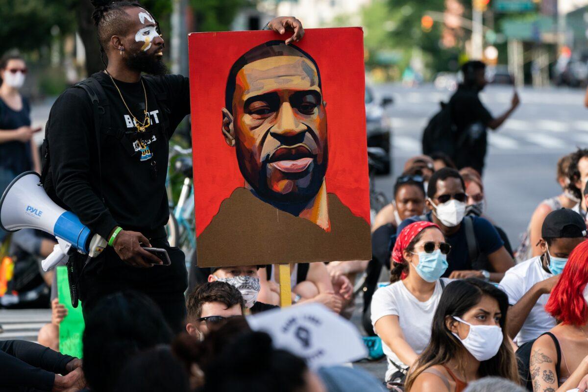 Um homem segura uma foto de George Floyd durante um protesto do Black Lives Matter na cidade de Nova Iorque em 18 de junho de 2020 (Jeenah Moon / Getty Images)