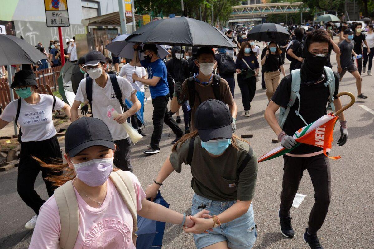 Os manifestantes correm depois de ouvir a polícia se aproximar durante uma manifestação contra uma nova lei de segurança nacional em Hong Kong em 1º de julho de 2020 (Alastair Pike / AFP via Getty Images)