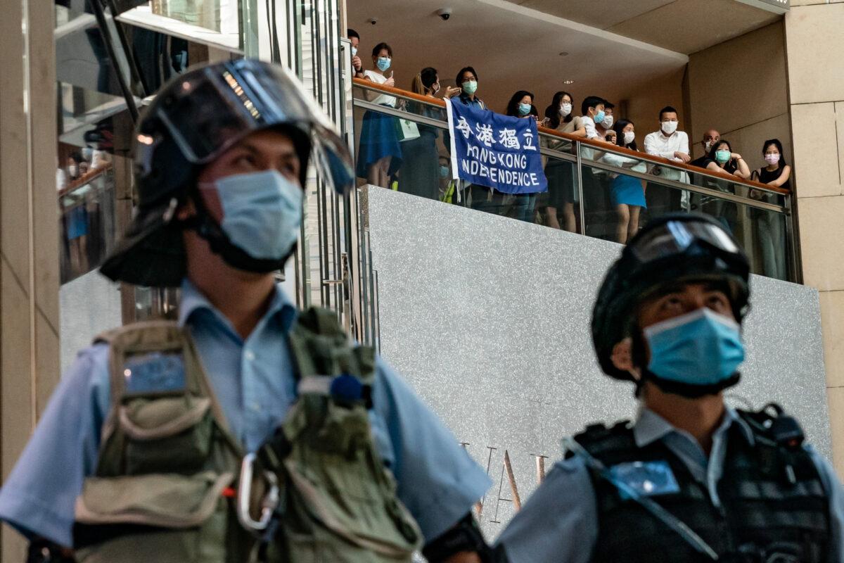 Apoiadores da democracia seguram uma bandeira da independência de Hong Kong e gritam slogans durante uma manifestação contra a lei de segurança nacional, enquanto a polícia de choque protege uma área em um shopping center em Hong Kong em 30 de junho de 2020 (Anthony Kwan / Getty Images)