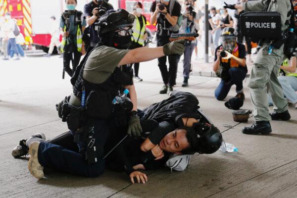 Um policial levanta sua pistola de spray de pimenta enquanto detém um homem durante uma marcha contra a lei de segurança nacional no aniversário da entrega de Hong Kong à China da Grã-Bretanha em Hong Kong, em 1º de julho de 2020 (Tyrone Siu / Reuters)
