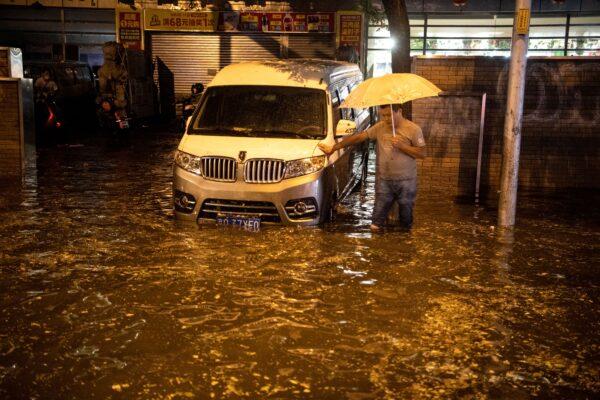 Um homem olha para uma rua inundada após uma chuva repentina em Pequim em 9 de agosto de 2020 (NOEL CELIS / AFP via Getty Images)