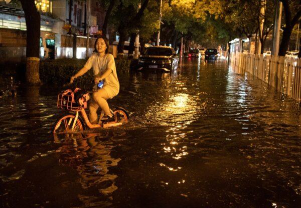 Uma mulher usa uma bicicleta para atravessar uma rua inundada após uma chuva repentina em Pequim em 9 de agosto de 2020 (NOEL CELIS / AFP via Getty Images)