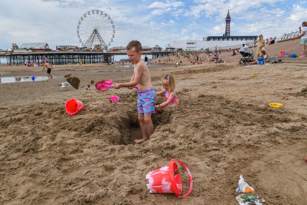 Crianças constroem castelos de areia na praia de Blackpool em Blackpool, Inglaterra, em 31 de julho de 2020 (Anthony Devlin / Getty Images)