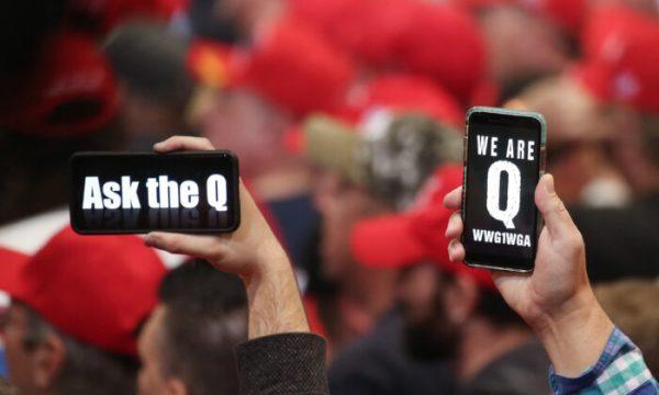 Pessoas seguram seus smartphones com mensagens relacionadas ao QAnon na tela em um comício em Las Vegas, Nevada, em 21 de fevereiro de 2020 (Mario Tama / Getty Images)